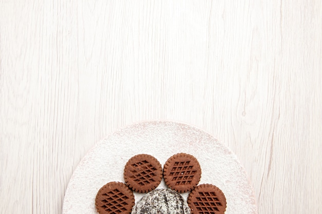 Top view yummy chocolate cookies with little cocoa cake on white