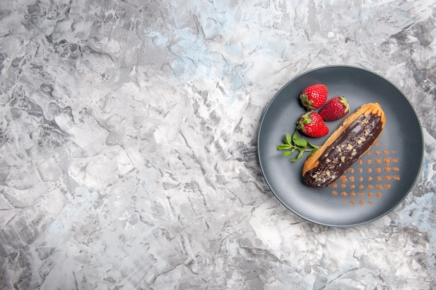Top view yummy chocolate eclairs with strawberries on light dessert cake fruit pie