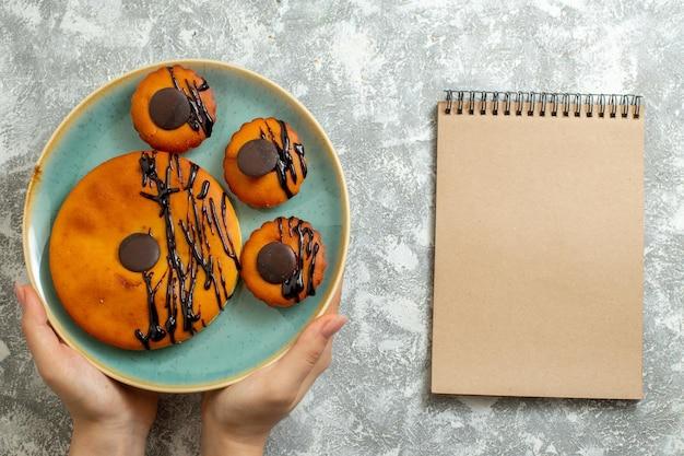 上面図ライトホワイトの表面ケーキビスケットデザート甘いクッキーパイのプレートの内側にチョコレートのアイシングが付いたおいしいココアケーキ