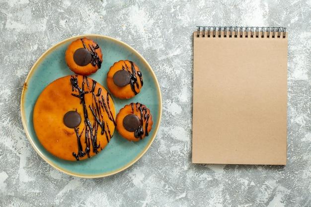 上面図白いデスクケーキビスケットデザート甘いクッキーパイのプレートの内側にチョコレートのアイシングとおいしいココアケーキ