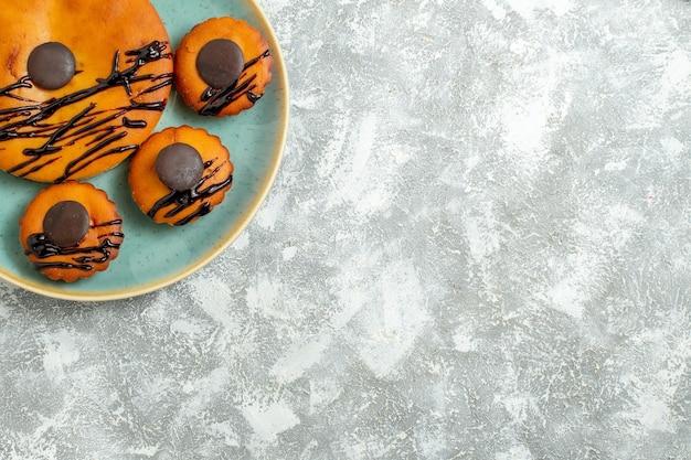 上面図白い机の上のプレートの内側にチョコレートのアイシングとおいしいココアケーキ甘いケーキビスケットデザートクッキーパイ
