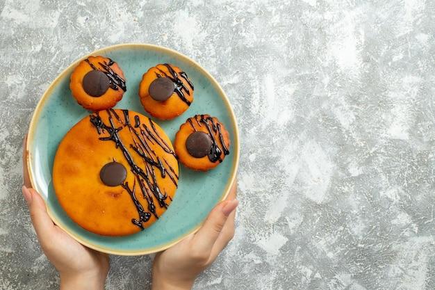 上面図白い表面のケーキビスケットデザート甘いクッキーパイのプレートの内側にチョコレートのアイシングが付いたおいしいココアケーキ 無料写真