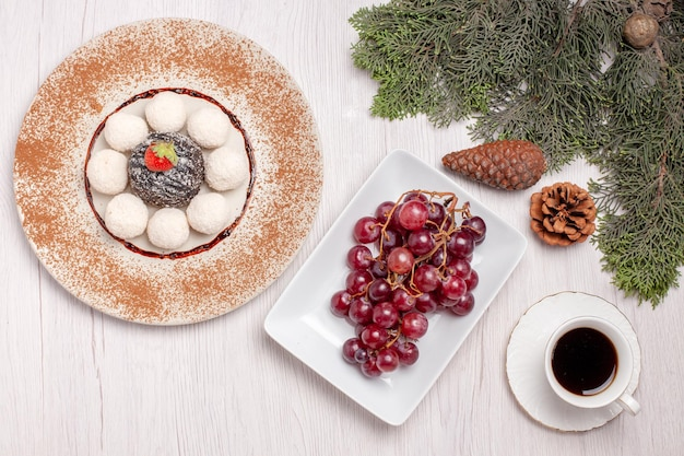 Vista dall'alto di deliziose caramelle al cocco con torta di tè e uva su bianco