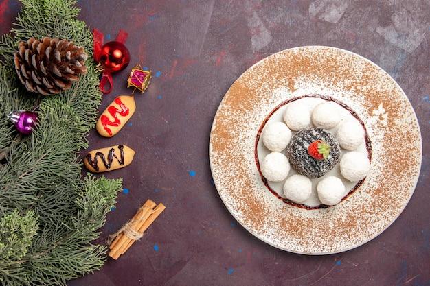 Vista dall'alto di deliziose caramelle al cocco con torta al cioccolato su nero