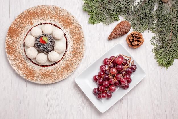 Vista dall'alto di deliziose caramelle al cocco con torta al cioccolato e uva su bianco