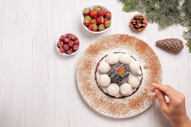 Vista dall'alto di deliziose caramelle al cocco con torta al cacao su bianco