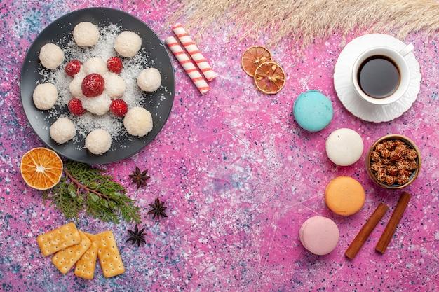 Vista dall'alto di deliziose caramelle al cocco con macarons francesi e tazza di tè sulla superficie rosa chiaro