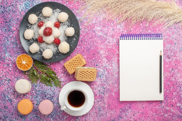 Top view of yummy coconut candies with fresh strawberries and waffles on pink surface