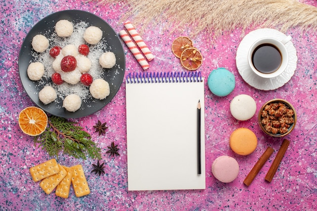 Top view of yummy coconut candies with macarons and cup of tea on light-pink surface