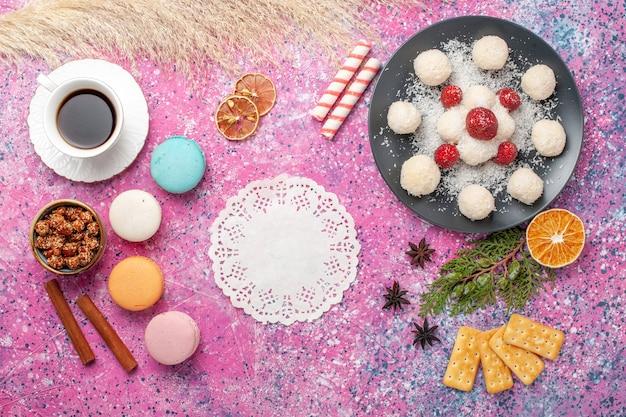 Vista dall'alto di deliziose caramelle al cocco con macarons e tazza di tè sulla superficie rosa