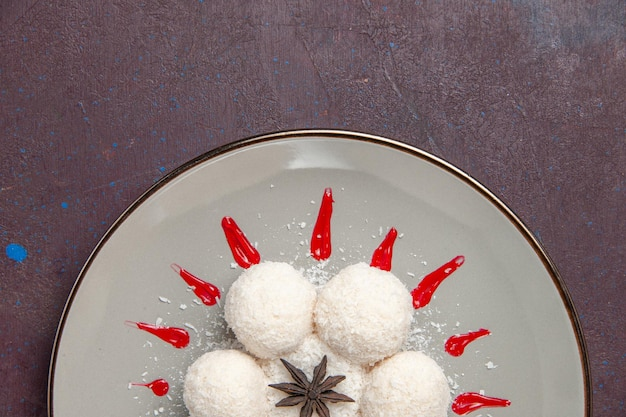Top view of yummy coconut candies with red icings on black