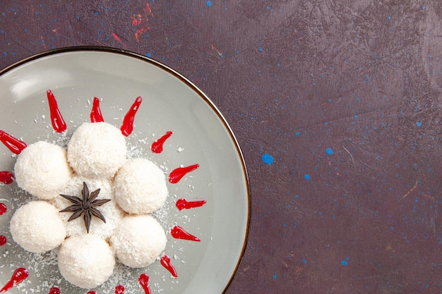 Vista dall'alto di deliziose caramelle al cocco con glasse rosse su fondo nero