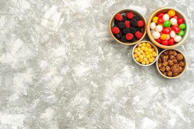 Вид сверху вкусные конфитюры с орехами и конфетами на светлом фоне сахарный чай сладкий торт печенье