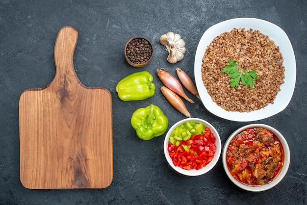 Vista dall'alto delizioso grano saraceno cotto con verdure sul grigio scuro