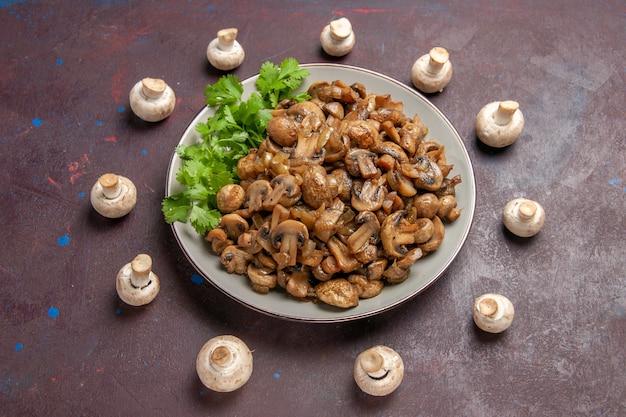 Vista dall'alto gustosi funghi cotti con verdure sulla scrivania scura