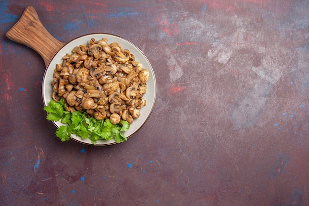 Vista dall'alto gustosi funghi cotti con verdure sul pavimento scuro