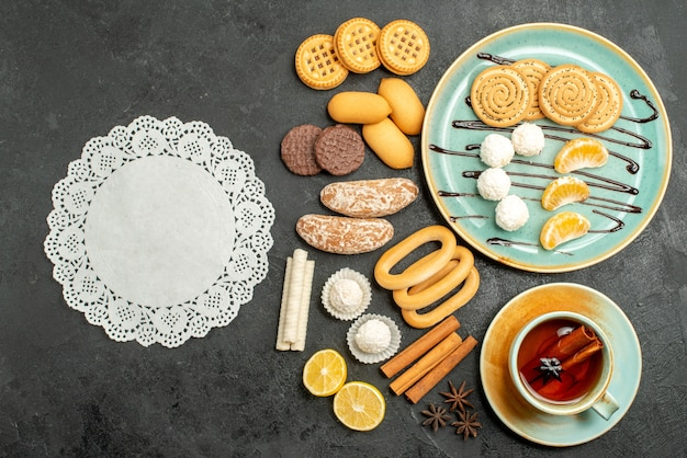 Top view yummy cookies with candies and biscuits on a grey background