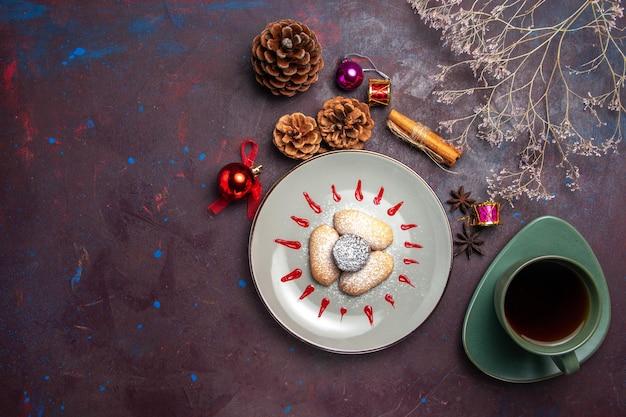Vista dall'alto di deliziosi biscotti con una tazza di tè su nero