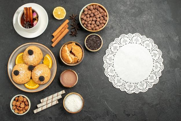 Vista dall'alto biscotti deliziosi con una tazza di tè sulla superficie scura torta torta zucchero dessert biscotto biscotti tè