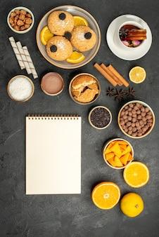 Top view yummy cookies with cup of tea and orange slices on dark floor cake pie sugar dessert biscuit tea