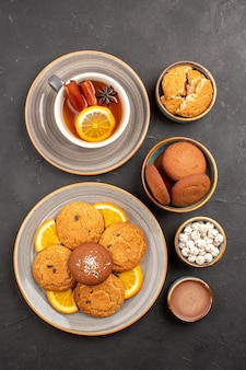 Top view yummy cookies with cup of tea and oranges on dark background biscuit fruit sweet cake cookie citrus