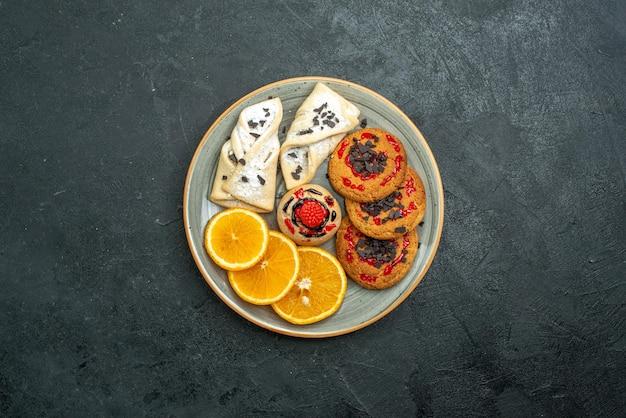 Вид сверху вкусное печенье с фруктовой выпечкой и дольками апельсина на темном фоне фруктовый сладкий торт пирог чай сахар