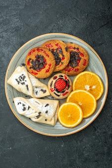 暗い背景にフルーティーなペストリーとオレンジスライスのトップビューおいしいクッキーフルーツ甘いケーキパイティーシュガー