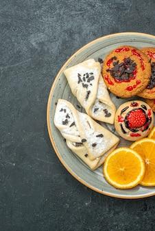 暗い机の上にフルーティーなペストリーとオレンジスライスが入ったトップビューのおいしいクッキーフルーツスイートケーキパイティーシュガー
