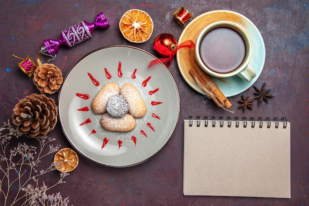 Top view of yummy cookies with red icings and cup of tea on black