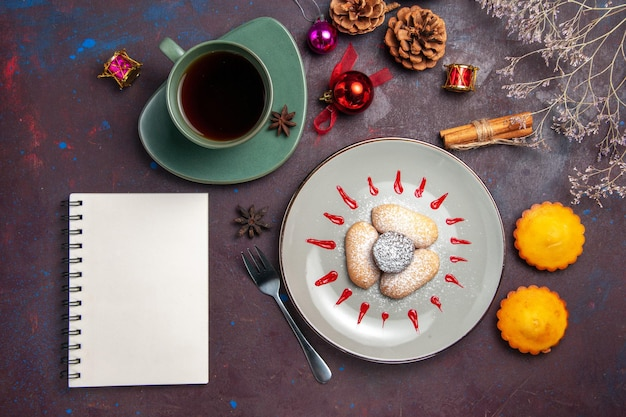 Top view of yummy cookies with sugar powder and cup of tea on black