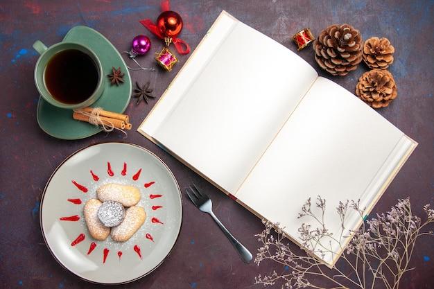 Vista dall'alto di deliziosi biscotti con zucchero in polvere e tazza di tè al buio