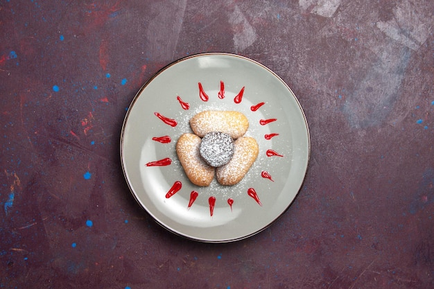 Top view of yummy cookies with sugar powder and red icing inside plate on dark