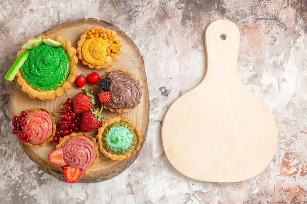 ライトテーブルのデザートビスケットの甘いケーキにフルーツとおいしいクリームケーキの上面図