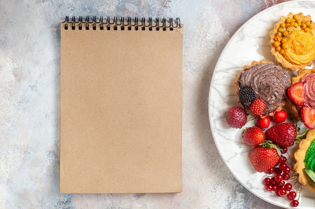 ライトテーブルの上の果物とおいしいクリームケーキの上面図ビスケットケーキデザート甘い