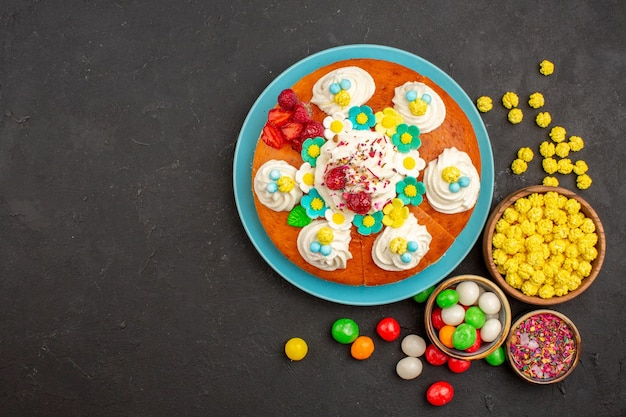 Top view of yummy cream pie with candies on dark
