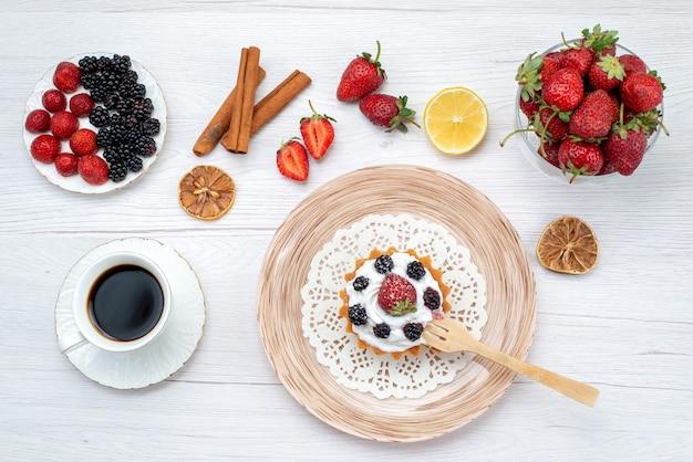 Vista dall'alto gustosa torta cremosa con frutti di bosco insieme a bacche di caffè alla cannella sul colore dolce della foto della torta leggera della scrivania