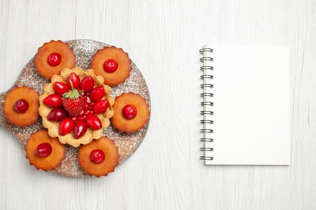 Vista dall'alto gustosa torta cremosa con torte e frutta sulla scrivania bianca