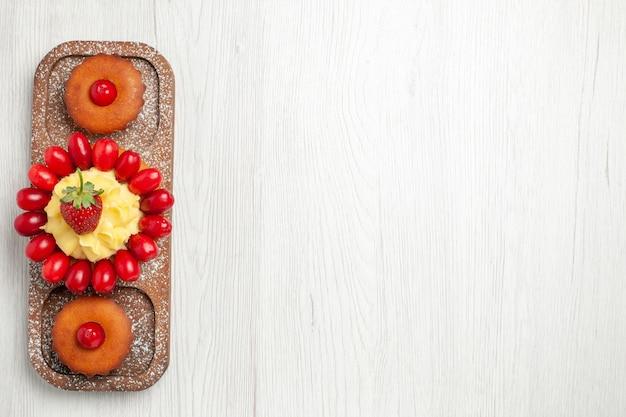Вкусный сливочный торт с пирожными на белом столе, вид сверху