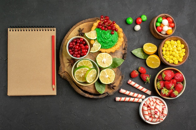 Top view yummy creamy cake with candies and fruits on dark floor sweet cookie biscuit
