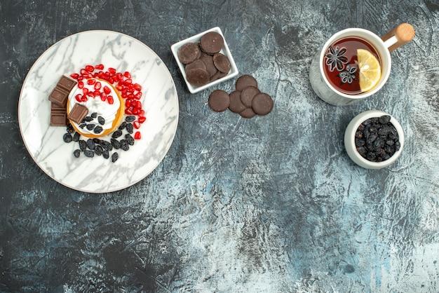 Вид сверху вкусный кремовый торт с шоколадным печеньем и чашкой чая на светло-темном фоне