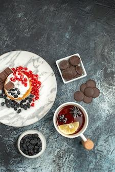 밝은 어두운 책상 쿠키 설탕 비스킷 달콤한 파이에 초코 비스킷과 차 한잔이있는 맛있는 크림 케이크