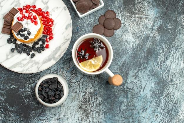 밝은 어두운 배경에 초코 비스킷과 차 한잔과 함께 상위 뷰 맛있는 크림 케이크