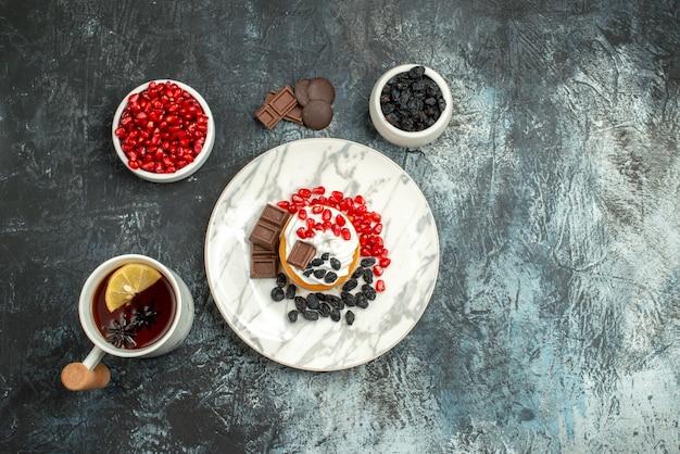 Vista dall'alto gustosa torta cremosa con biscotti al cioccolato e tazza di tè sullo sfondo chiaro-scuro