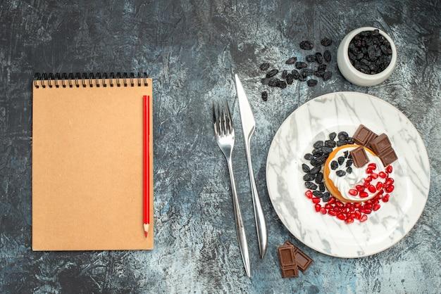Вид сверху вкусный сливочный торт с шоколадом и изюмом на светло-темном фоне