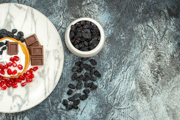 Вид сверху вкусный сливочный торт с шоколадными гранатами и изюмом на светло-темном фоне Бесплатные Фотографии