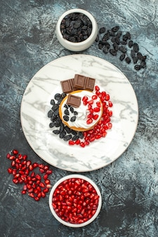 밝은 어두운 배경에 초콜릿 석류와 건포도와 상위 뷰 맛있는 크림 케이크