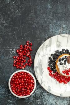 Vista dall'alto gustosissima torta cremosa con melograni al cioccolato e uvetta su sfondo chiaro-scuro