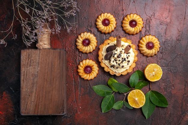 暗い床のデザート甘いビスケットケーキにクッキーとおいしいクリーミーなケーキの上面図