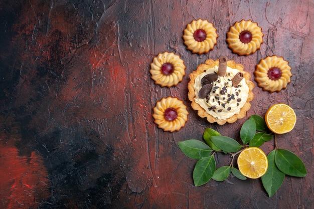 暗いテーブルの上のクッキーとおいしいクリーミーなケーキの上面図デザート甘いビスケットケーキ