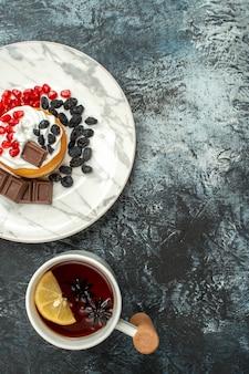 明るい-暗い背景の上のお茶のカップとトップビューおいしいクリーミーなケーキ